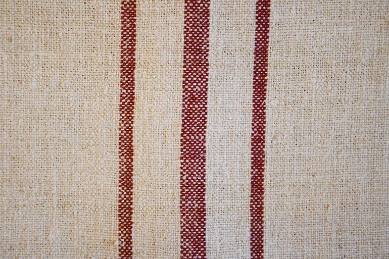 Red lines on white textile texture – closeup
