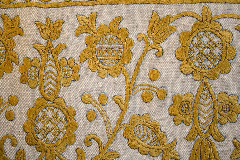 Yellow flower on textile texture – closeup