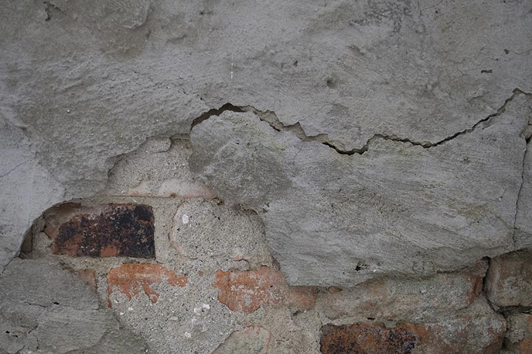 Grey cracked crumbling wall texture