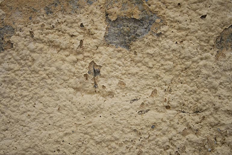 Yellow plaster closeup wall texture