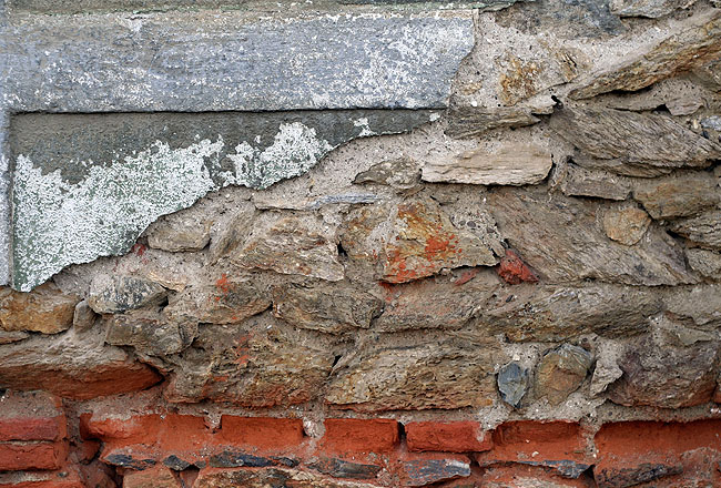 Cracked wall with bricks and stone