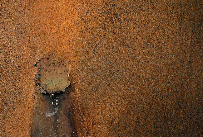 Rusty metal texture with cracked hole