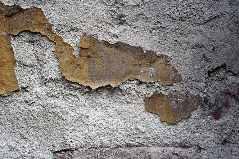 Grey cracked wall texture with yellow plaster